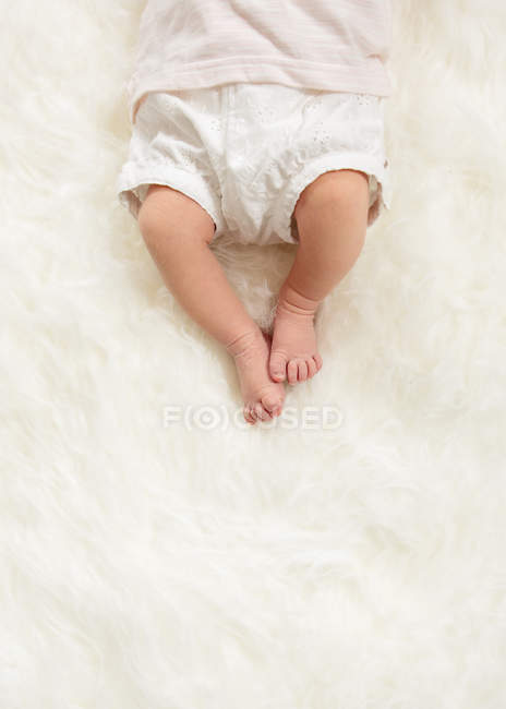 Baby feet on furry cover, elevated view — Stock Photo