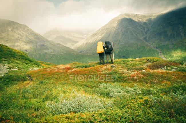 Condizione delle coppie viaggiatore sul prato verde della montagna — Foto stock