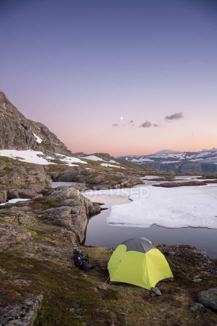 Подорожі намет на березі озера з гори на тлі — стокове фото