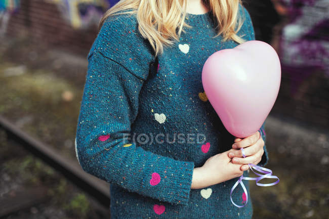 Partial view of woman in sweater holding pink heart shape balloon — Stock Photo