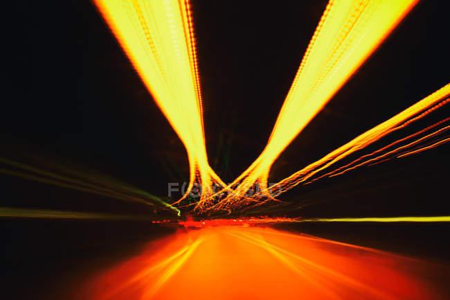 Размытие движения на дороге ночью в движении — стоковое фото
