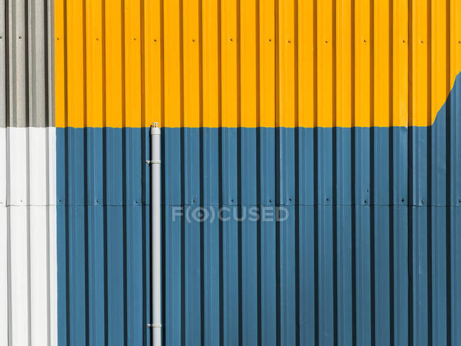 Parete di edificio verniciato blu giallo con strisce e linee, completo di cornice immagine — Foto stock