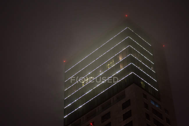 Exterior shot of building facade at night in fog — Stock Photo