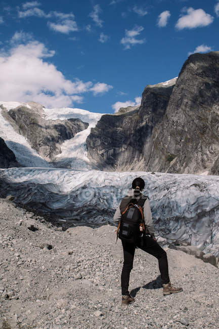 Traveler woman in mountains looking at glacier — Stock Photo