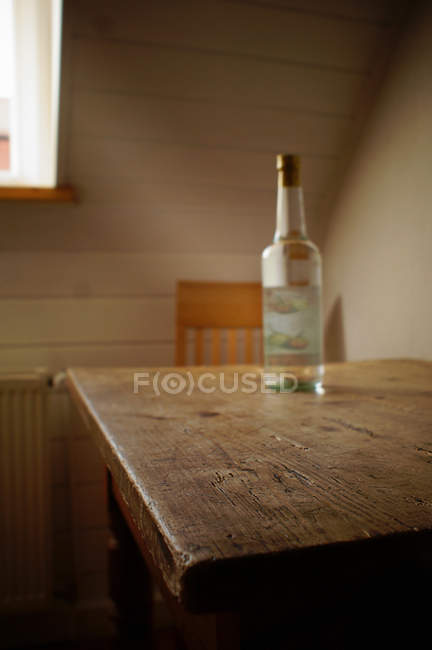 Bottle of alcoholic beverage on shabby wooden table — Stock Photo