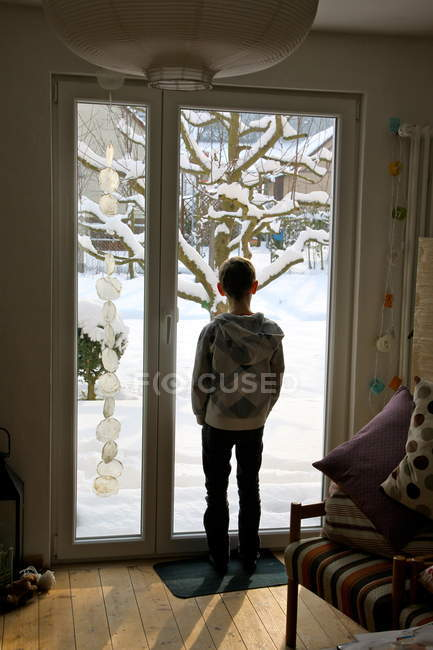 Rear view of young boy at home looking out of window at snow — Stock Photo
