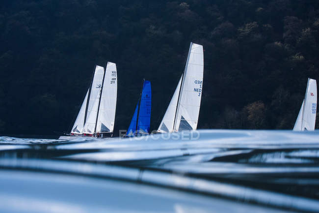 Sails of yachts regatta over water surface level — Stock Photo