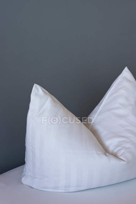 Daytime view of one white striped pillow near gray wall — Stock Photo