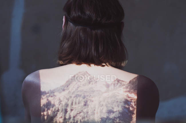 Head and shoulders, back view of woman with reflection of mountains on her back with slide projector — Stock Photo