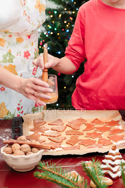 cropped view of woman with daughter making christmas cookies stock photo - Making Christmas Cookies