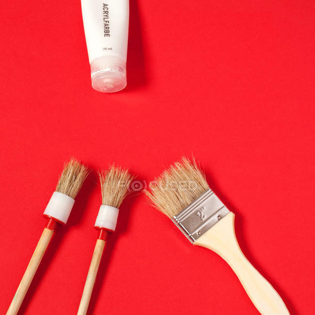 Paint brushes and paint tube isolated on red background — Stock Photo