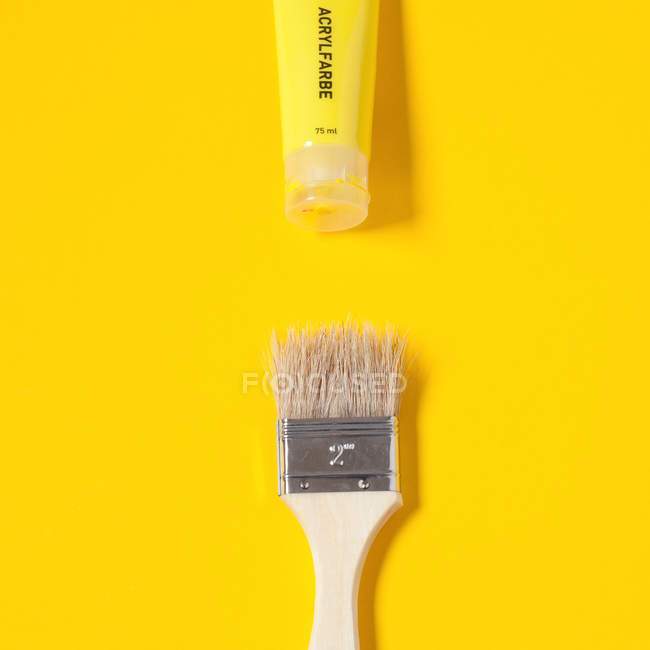 Paint brush and paint tube isolated on yellow — Stock Photo