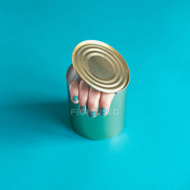 Human fingers in opened tin — Stock Photo