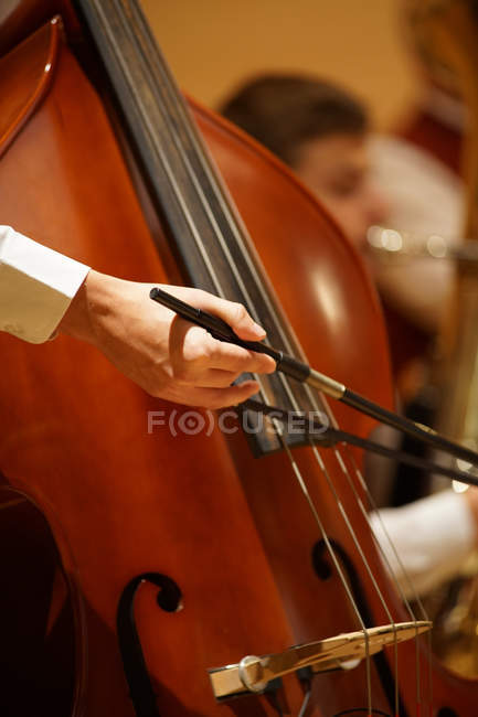 Partial view of musician playing wooden double bass in orchestra — Stock Photo