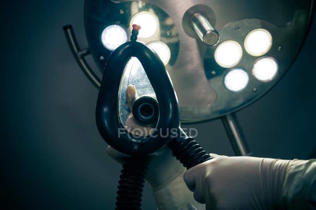 Doutor, segurando máscaras de oxigênio de anestesia, operar sala com iluminação cirúrgica — Fotografia de Stock