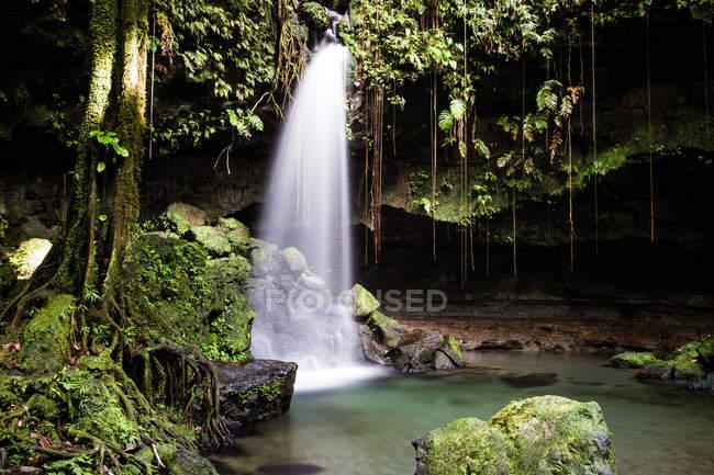 Waterfall falling into shallow lake — Stock Photo
