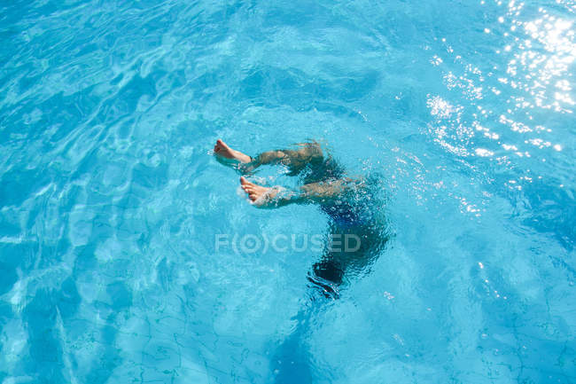 Man jumping in pool blue water — Stock Photo
