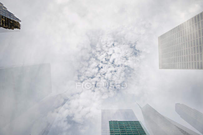 Vista inferiore di grattacieli contro il cielo nuvoloso — Foto stock