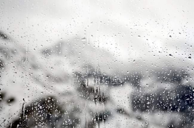 Abstrait backdrop avec de l'eau tombe sur la vitre — Photo de stock