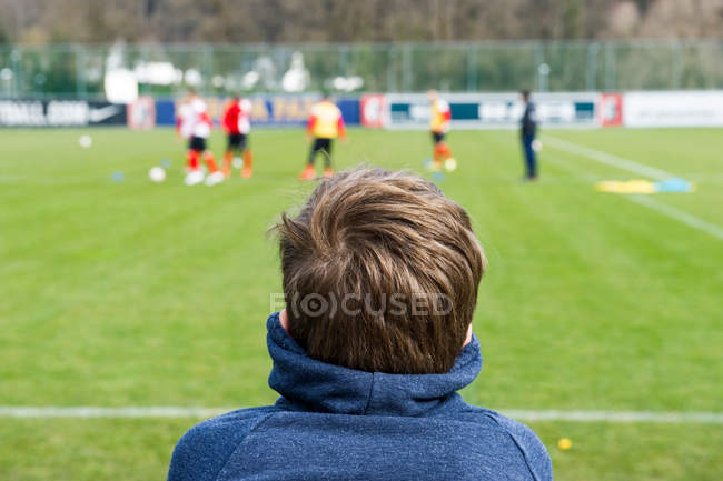 Rear view of boy looking at soccer field — Stock Photo