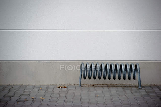 Exterior shot of white building wall with iron spiral tube — Stock Photo