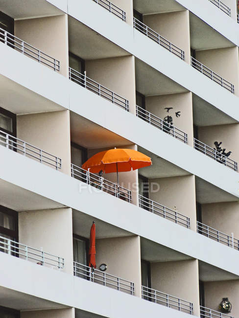 Exterior shot of building facade with balconies and orange umbrella — Stock Photo