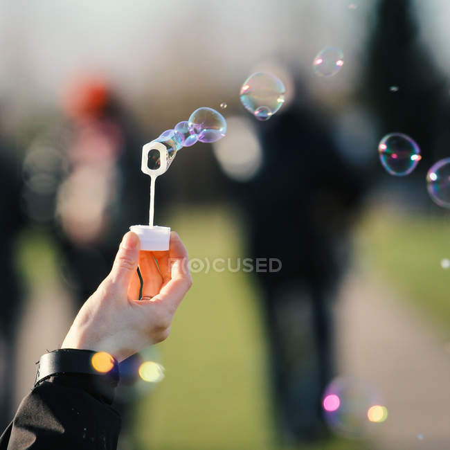 Hand holding colorful soap bubbles — Stock Photo