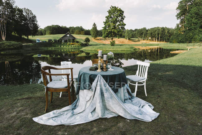 Table setting in green field — Stock Photo