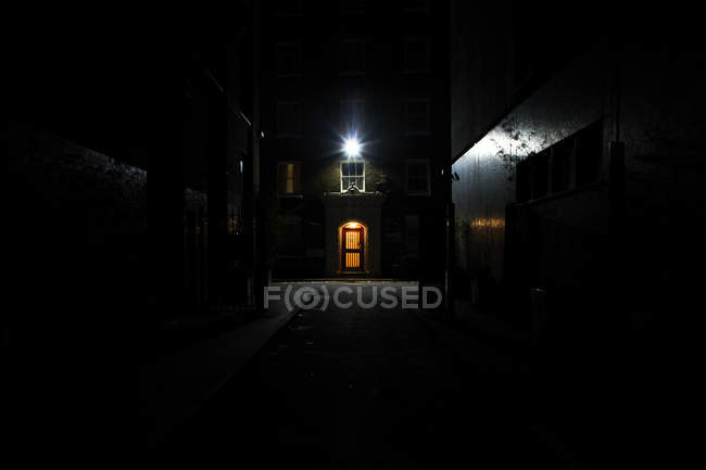 Gloomy dark passage in residential area among houses at late night, lanter above doorway — Stock Photo