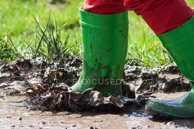 Vue rapprochée des pieds de l'enfant en caoutchouc vert bottes marcher dans la boue — Photo de stock