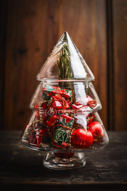 Glass Vase In Shape Of Christmas Tree With Baubles On Rustic Table