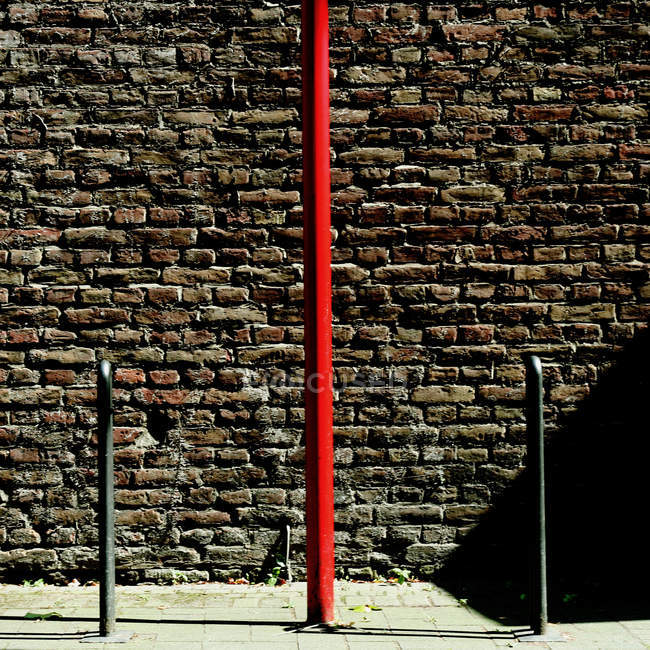Building brick wall surface and red iron tube — Stock Photo