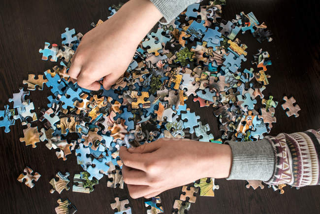 Child hands collecting puzzle, overhead view — Stock Photo