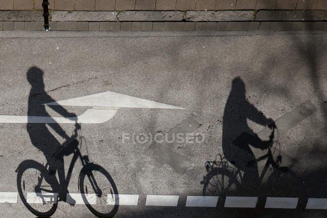 Асфальтовая дорога с тенями с велосипедного люди на велосипедах — стоковое фото