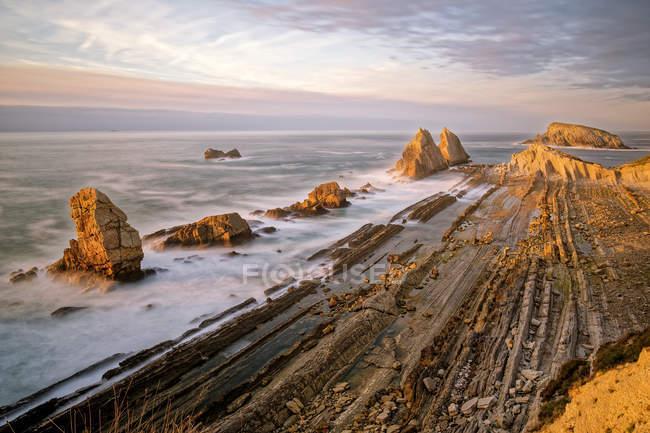 Sunset over rocky sea beach — Stock Photo