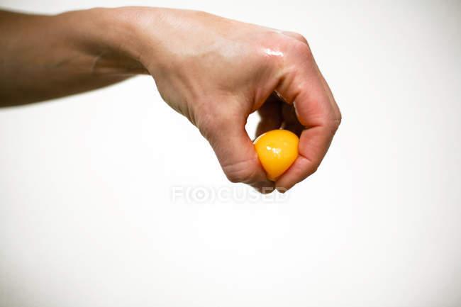 Menschliche Hand halten Eigelb — Stockfoto