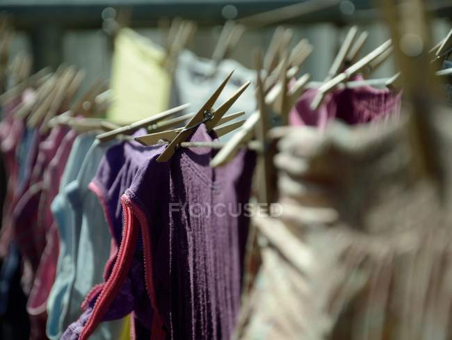 Fabric clothing on handles with clothes pegs — Stock Photo