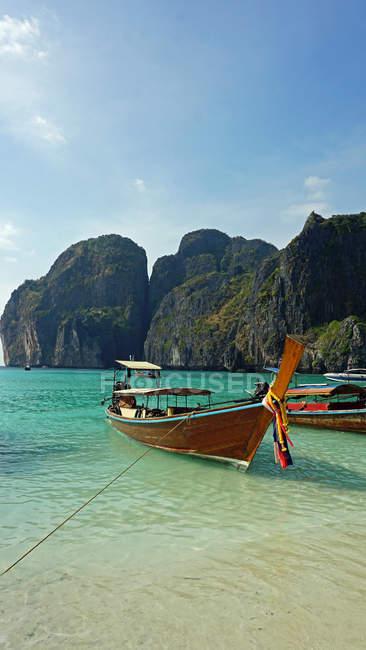 Bateaux dans l'océan au bord de la mer avec des falaises rocheuses — Photo de stock