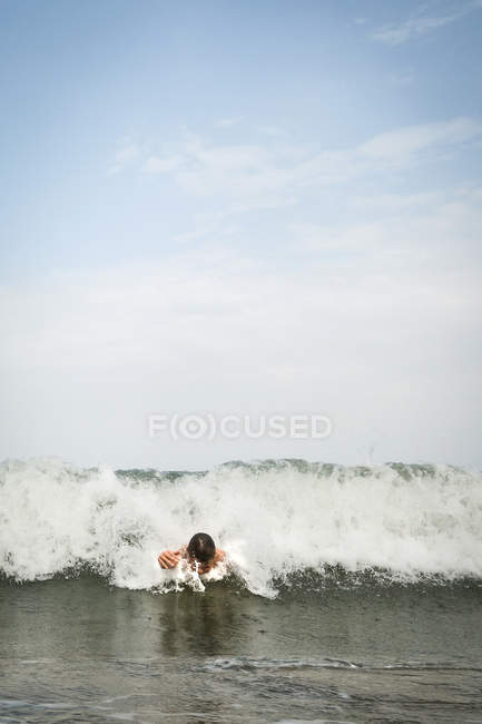 Boy swimming in the sea, wave on background — Stock Photo