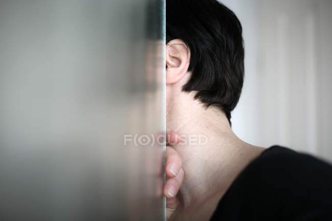 Partial view of woman hiding behind glass door, head and shoulders — Stock Photo