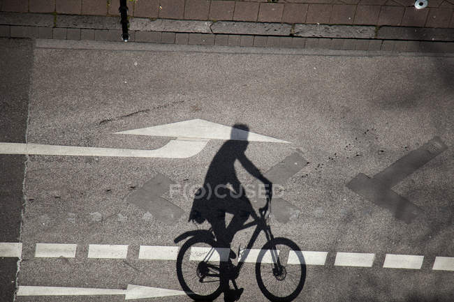 Asphalt road with arrow sign and shadow of cycling person on bicycle — Stock Photo