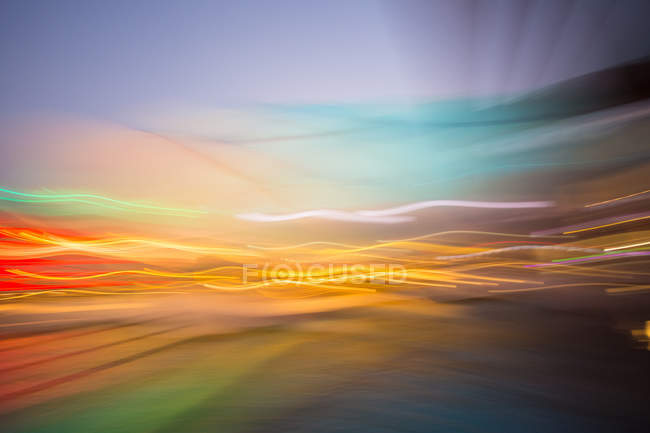 Long exposure shot of colorful moving lights over water surface — Stock Photo