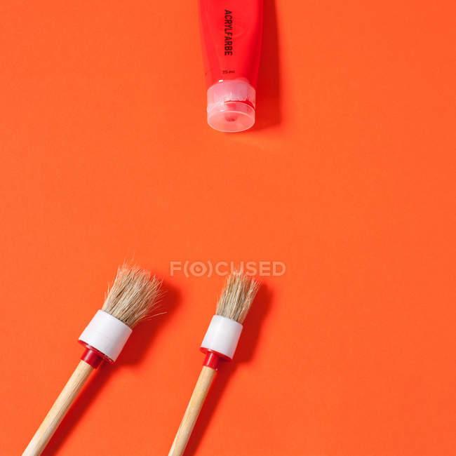 Paint brushes and paint tube isolated on orange background — Stock Photo
