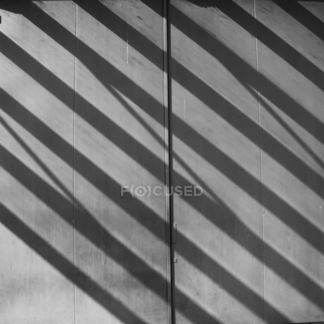 Full frame image of grey wall with shadows of lines — Stock Photo