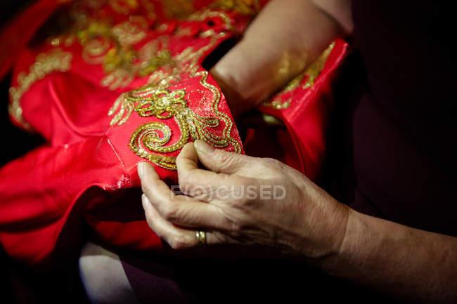 Крупным планом вид руки, пошив традиционной одежды орнамент — стоковое фото