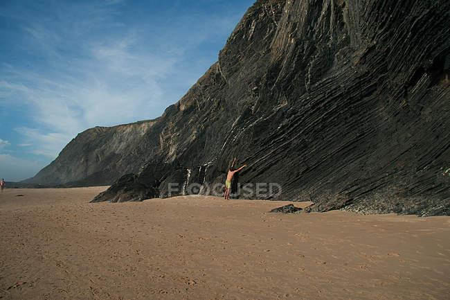 Plage de sable avec des montagnes Rocheuses, homme escalade sur la montagne — Photo de stock