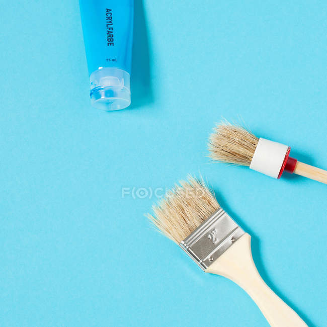 Paint brushes and paint tube isolated on blue background — Stock Photo