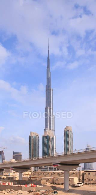 Vista diurna del Burj Khalifa con rascacielos y puente en Dubai - foto de stock