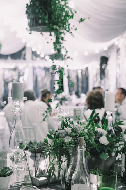 Scene with people at party under white tent decorated with green plants, flowers and lights — Stock Photo