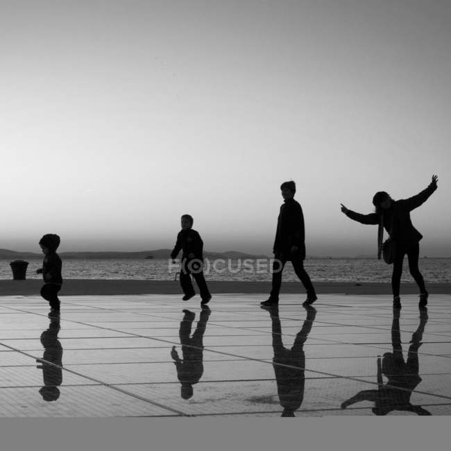 Silhouettes of children at the seaside embankment — Stock Photo